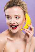 happy naked young woman holding yellow decorative banana near ear isolated on purple