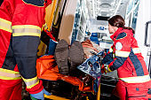 Paramedics transportating patient on gurney in ambulance car