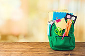 Back to school concept with bag backpack and school supplies on wooden table over abstract bokeh background