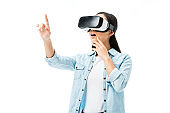 shocked woman in denim shirt with virtual reality headset pointing with finger isolated on white