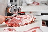 Close up of meat pieces and worker hands in gloves cutting.