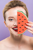 attractive naked young woman holding slice of decorative watermelon isolated on purple