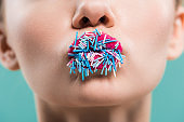 cropped view of woman with sprinkles on lips isolated on blue