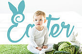 child sitting near savoy cabbage and decorative bunny on green grass with blue Easter lettering