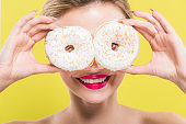 cheerful woman covering eyes with tasty doughnuts isolated on yellow