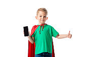 front view of smiling preschooler kid in red hero cloak showing smartphone with blank screen and showing thumb up isolated on white