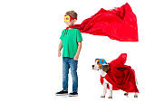 full length view of smiling preschooler child and beagle dog in masks and red hero cloacks isolated on white