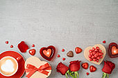Valentine's day background with coffee cup, heart shape chocolate, candles, rose flowers and gift boxes.