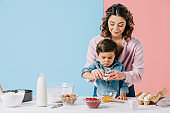 smiling mother with concentrated little son cooking together at white kitchen table on bicolor background
