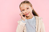 smiling and cute kid talking on smartphone isolated on pink