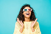 happy curly african american woman laughing and gesturing in 3d glasses isolated on blue