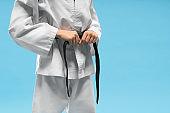 Karate girl in white kimono holding hands on belt.