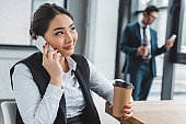 smiling young asian businesswoman holding paper cup and talking by smartphone in office