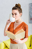 elegant young woman in pearl necklace holding book and drinking coffee