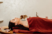 side view of woman lying under towel on massage table