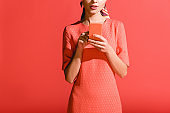cropped view of woman in living coral dress using smartphone on red