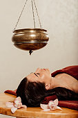 relaxed young woman lying under shirodhara vessel during ayurvedic procedure