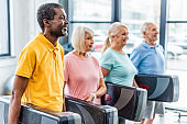 selective focus of multiethnic senior sportspeople holding step platforms at gym