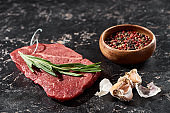 raw beef steak with rosemary twig near small bowl with peppercorns mix and garlic on black marble surface