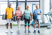 smiling multiethnic senior sportspeople holding step platforms at gym