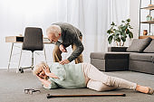 supportive retired husband looking at senior wife lying on floor and holding head