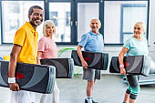laughing multiethnic sportspeople holding step platforms at gym