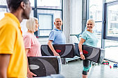 joyful multiethnic senior sportspeople holding step platforms at gym