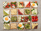 Top view of toasts with fried eggs, cut vegetables and fruits on textured surface