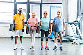 cheerful multiethnic senior sportspeople holding step platforms at gym