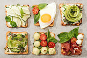 Top view of toasts with vegetables, fried egg and prosciutto on textured surface
