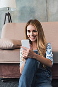 young woman using smartphone and sitting near sofa