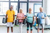 multicultural senior sportspeople holding step platforms at gym