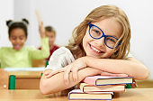 Front view of pretty female student looking at camera and laughing while lying on books in classroom. Smart girl in glasses leaning on equipment, posing and smiling at school. Concept of learning.