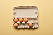 top view of brown organic eggs in cardboard box on yellow background