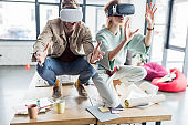 selective focus of excited female and male architects gesturing with hands while having virtual reality experience in loft office