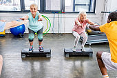 smiling senior multiethnic sportspeople synchronous doing squats on step platforms at gym