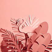 bunch of paper cut palm leaves and flamingo on pink background