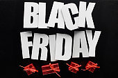 top view of black Friday lettering and red presents isolated on black