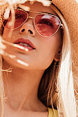 pensive attractive girl in sunglasses and straw hat looking up