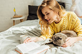 beautiful young woman reading book while lying in bed with scottish fold cat