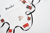 top view of calendar with November 29 marked date on white background with black ribbon and presents