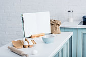 blank opened cookbook on table with cooking utensils and bakery ingredients