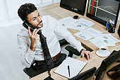high angle view of bi-racial trader talking on telephone and sitting near computer with graphs