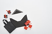 top view of black envelope with blank card near decorative gift boxes and shopping bag on white background