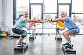 happy senior multiethnic sportspeople synchronous doing squats on step platforms at gym