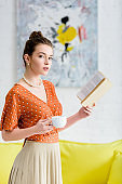elegant young woman in pearl necklace holding book and cup while looking at camera