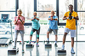 happy senior multicultural sportspeople synchronous exercising with dumbbells on step platforms at gym