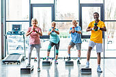 senior multicultural sportspeople synchronous exercising with dumbbells on step platforms at gym