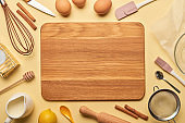 top view of empty wooden chopping board with cooking utensils and ingredients on yellow background