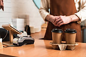 Cropped view of barista in brown apron and disposable cups of coffee